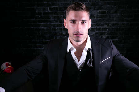Portrait of handsome man wearing tuxedo with open shirt looking at camera 版權商用圖片