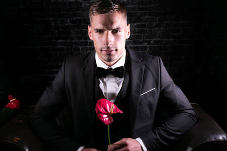 Portrait of handsome man wearing tuxedo with bowtie holding a flower and scowling at camera 版權商用圖片