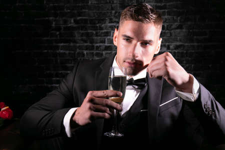 Portrait of handsome stylish man wearing a tuxedo holding up glass of sparkling wine and looking at camera. 版權商用圖片