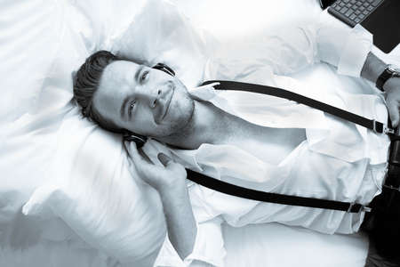 Handsome business man with suspenders lying on hotel room bed smiling while listening to music on headphones