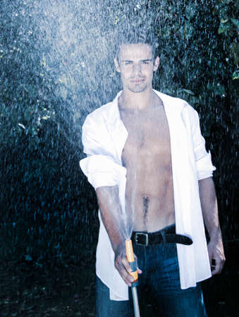 Handsome male with muscular body and open shirt showering with garden hose on sunny day