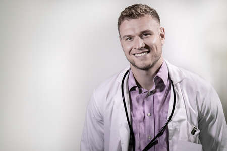 Handsome male doctor smiling at camera in front of white backdrop with room for copy 版權商用圖片