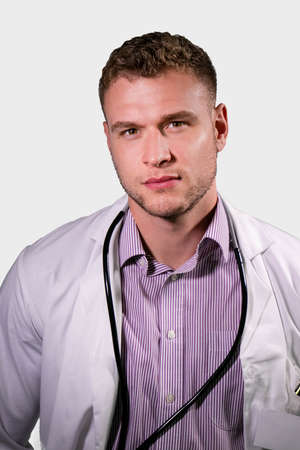 Serious handsome male doctor wearing white lab coat looking at camera 版權商用圖片