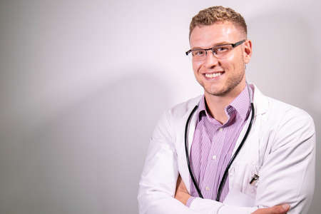 Portrait of handsome male doctor, smiling and looking at camera