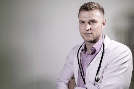 Handsome doctor with stethoscope and folded arms looking at camera 版權商用圖片