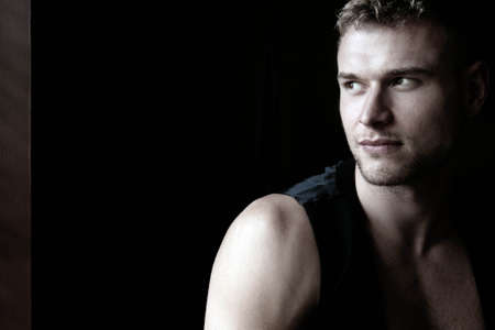Portrait of handsome young man looking away from camera with open black shirt revealing muscular pecs