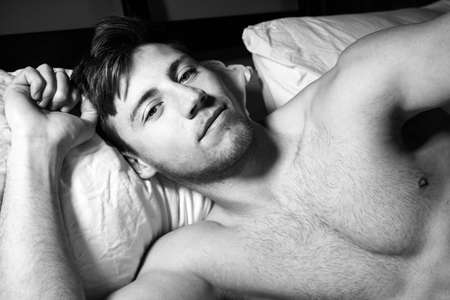 Handsome muscular man with beard lying in bed looking at camera
