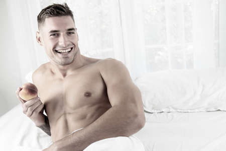 Sexy smiling muscular man lying shirtless in bed revealing pecs and sixpack abs holding a peach.