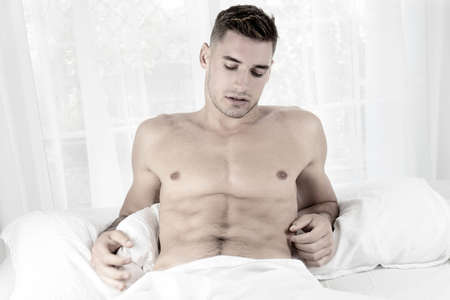 Handsome naked muscular man with stubble, sixpack abs lying in bed covered with sheet 版權商用圖片