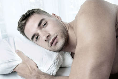 Handsome hairy naked muscular man with beard sixpack abs lying in bed covered with sheet 版權商用圖片