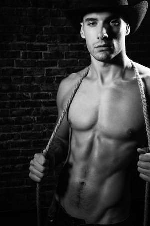 Portrait of handsome shirtless cowboy looking at camera wearing hat with defined pecs and sixpack abs, holding rope
