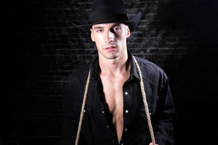 Portrait of handsome cowboy looking at camera wearing hat with open black shirt revealing defined pecs and sixpack abs 版權商用圖片