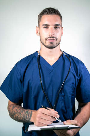 Smiling handsome male doctor in blue scrubs with arms folded in front of white backdrop