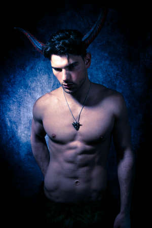 Sexy shirtless male devil with horns and muscular body showing pecs and abs