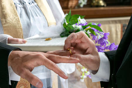 Gay men exchanging wedding rings in front of vicar in church holding bible and ring in background
