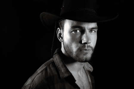 Portrait of handsome male cowboy wearing open chequered shirt and hat revealing sixpack abs isolated on black Reklamní fotografie