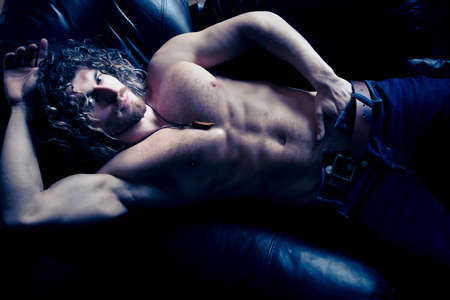 Portrait of attractive shirtless muscular man with beard and sixpack abs lying in leather armchair, looking at camera