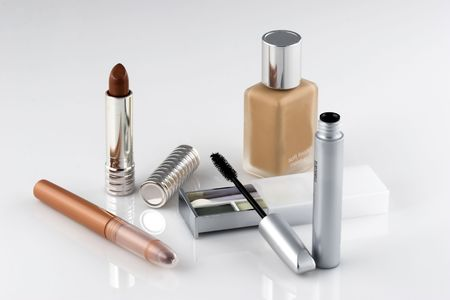makeups: An assortment of makeups.  On a white reflective background.