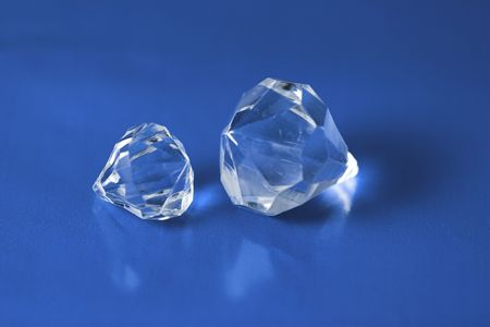 lavish: Two diamonds on a blue reflective background.  One large diamond and on smaller.