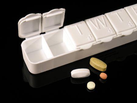 Abteile: Pillbox mit F�chern f�r jeden Tag der Woche mit 2 Tage weg. Die Tage der Woche sind auch in Blindenschrift. Vier Tabletten daneben. Auf einem schwarzen Hintergrund reflektierend.  Lizenzfreie Bilder
