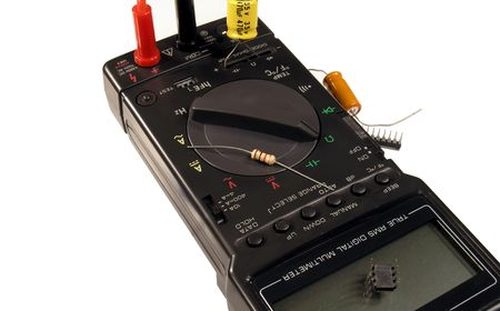 Digital multimeter with resistors, capacitors, and ICs.  On white background. photo