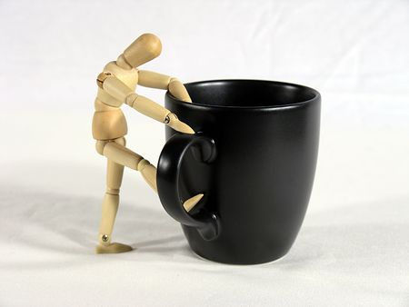 caffiene: Mannequin climbing into a coffee cup.  Metaphor for starting the day. Stock Photo