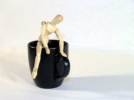 caffiene: Wooden mannequin climbing out of a black coffee cup.