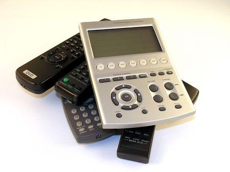 tv remotes: Master remote on a pile of older remotes.