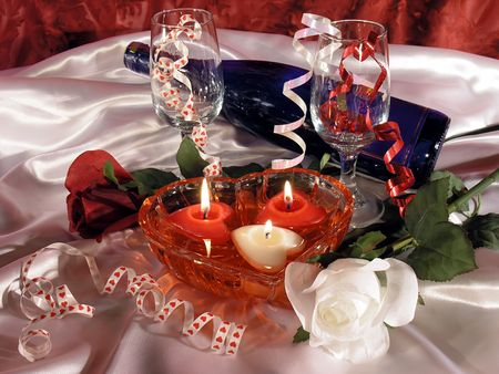 sweetest:  still life. Red and white roses, bottle of wine, two glasses, and heart shaped floating candles in a heart shaped dish. On a white silk background.