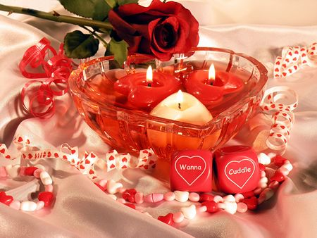 Heart shaped dish with three heart shaped floating candles. Romantic dice that say