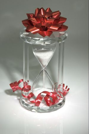 Hourglass with red bow and ribbon.  Metaphor for The Gift Of Time.