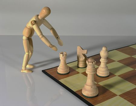 conspire: Wooden mannequin moving chess pieces. Stock Photo