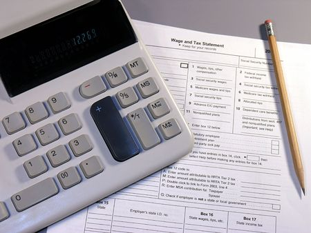 Calculator with an IRS Wage And Tax Statement form. Stock Photo