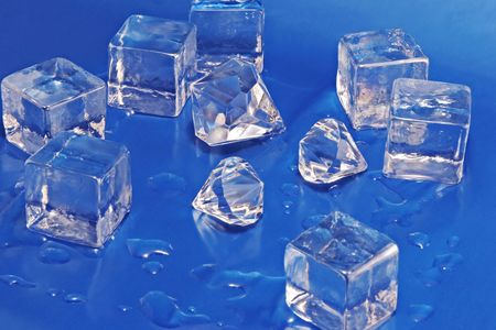 Diamonds and melting ice cubes on a field of blue. Stock Photo