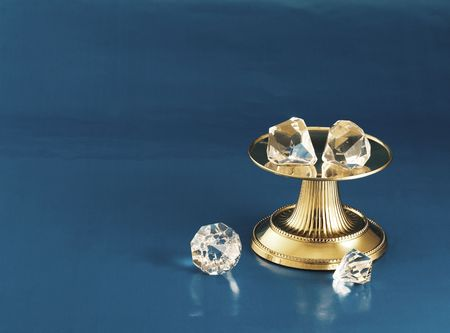 Gold pedestal with diamonds on it and two beside it.  Blue background.