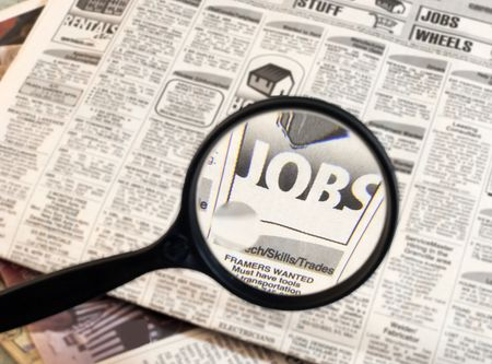 looking for work: Newspaper opend to the want ads.  Magnifying glass highlighting the word Jobs. Stock Photo
