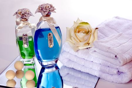 soothe: Bath oils reflected in a mirror, towel, washcloth, and a rose.