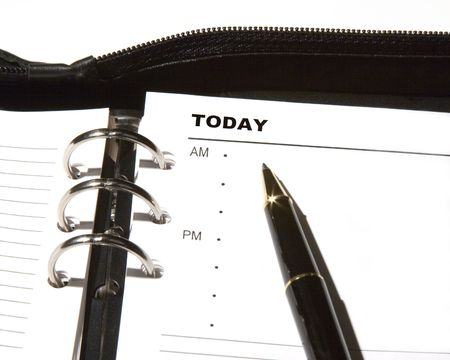 Open day planner with a ballpoint pen pointing to TODAY.