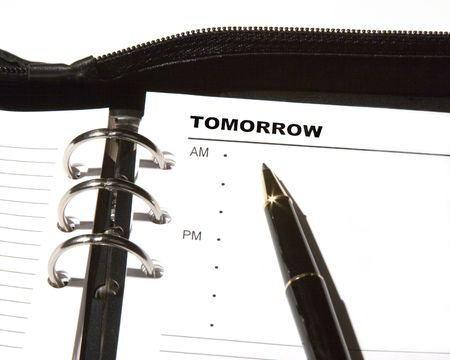 Open day planner with a ballpoint pen pointing to TOMORROW.