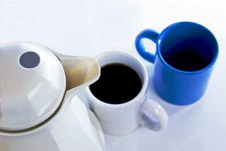 caffiene: Top view of a coffee pot  caraffe and two cups.  Focus is on the spout with the cups slightly out of focus.