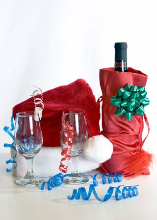 merriment: Christmas party.  Wine in a gift bag, wineglasses, and a Santa hat.