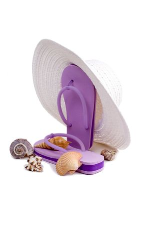Floppy white sun hat, flip flops, and seashells isolated on a white background.  A day at the beach.