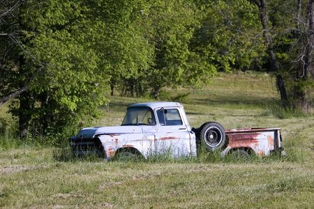 junked: An old abandoned pickup truck sitting in a grassy field.