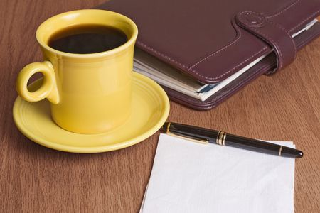 coffeecup: Bright yellow cup of coffee, dayplanner, pen, and napkin.  Business meeting scene.