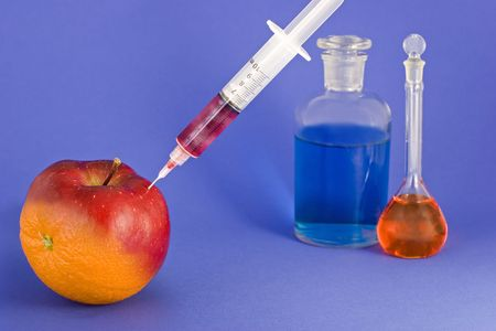 Altering the DNA of an orange to make an apple.  Syringe is filled with a cloudy liquid being injected into an orange.  Bottles of colored liquids in the background.  On blue paper background.