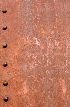 bolted: Rusty metal for background.  Six rusted rivets down the left hand side.