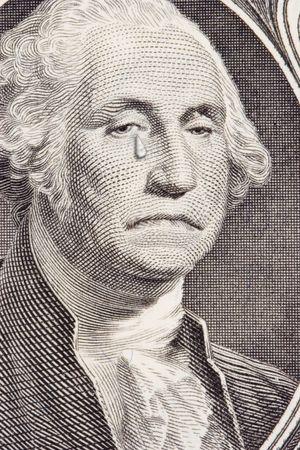 george washington: Closeup de un entristecido George Washington en la factura de un d�lar. George tiene un desgarro de streaming en la mejilla derecha. Met�fora para el pobre desempe�o de los EE.UU. D�lar.  Foto de archivo