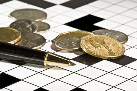 perplexing: Ejecutivo del bol�grafo y monedas en un crucigrama en blanco. Imagen conceptual de problemas de dinero, la resoluci�n de problemas, brain storming, etc