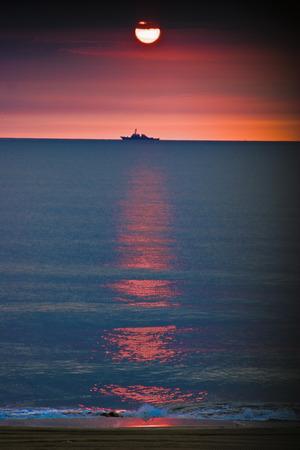 A lone US Navy battleship on the distant horizon as the sun slowly rises over the Atlantic Ocean.  Off the coast of Virginia.