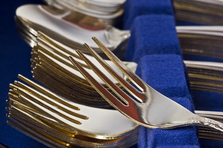 Closeup of a boxed set of gold plated flatware.  Stacks of forks, spoons, and knives. Stock Photo - 1536687